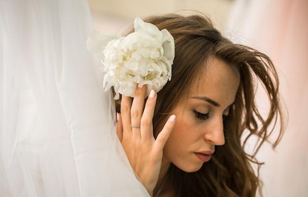 Belle jeune fille aux cheveux longs avec de vraies fleurs entre les mains du doux mystère