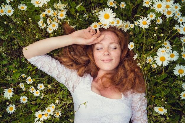 Belle jeune fille aux cheveux roux bouclés dans le champ de camomille
