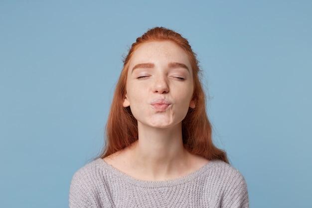 Belle jeune fille aux cheveux roux envoie un baiser debout avec les yeux fermés, les lèvres sont pliées pour un baiser