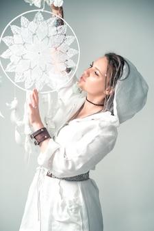 La belle jeune fille aux dreadlocks dans un style bohème tient un capteur de rêves dans ses mains. méditation et relaxation