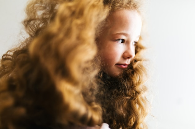 Belle jeune fille aux longs cheveux bouclés sourit et regarde au loin