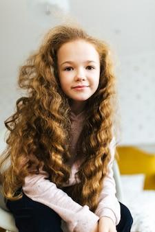 Belle jeune fille aux longs cheveux bouclés sourit et regarde dans l'appareil photo