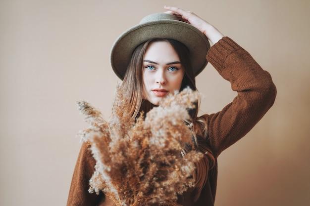 Belle jeune fille aux longs cheveux bruns en chapeau de feutre et pull en tricot brun avec des fleurs séchées en mains sur fond beige