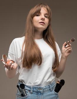 Une belle jeune fille aux longs cheveux rustiques ondulés, maquillage nud, vêtu d'un maillot blanc, tient un pinceau de maquillage et blush