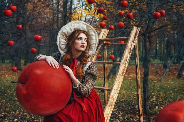 Belle jeune fille aux pommes rouges dans le jardin d'automne