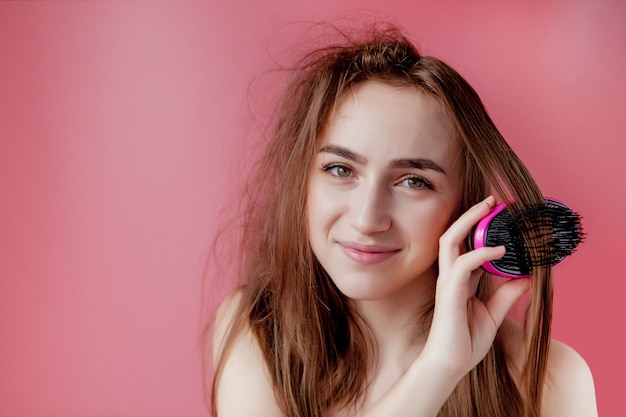 Belle jeune fille ayant des problèmes tout en cheveux sur fond rose