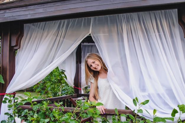Belle jeune fille blonde aux cheveux longs mince et heureuse dans un gazebo.