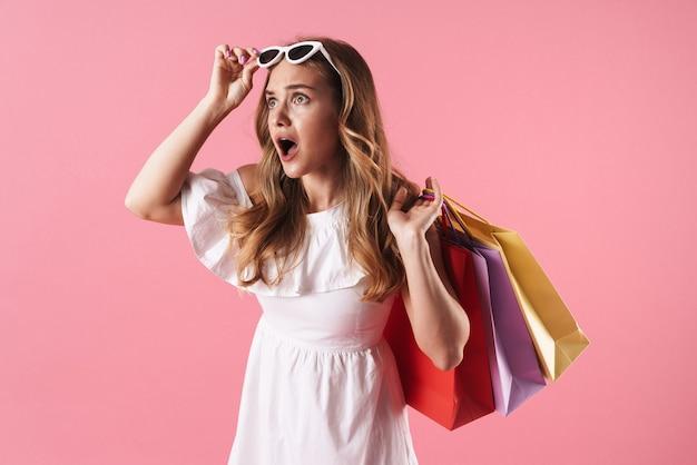 Belle jeune fille blonde choquée portant une robe d'été isolée sur un mur rose, portant des sacs à provisions