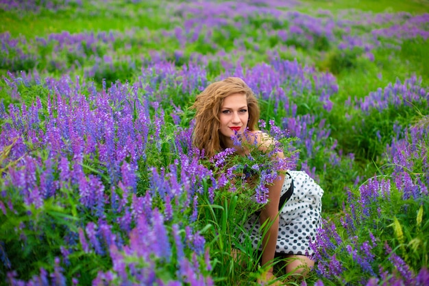 Belle jeune fille blonde dans un champ vert parmi les fleurs sauvages violettes.