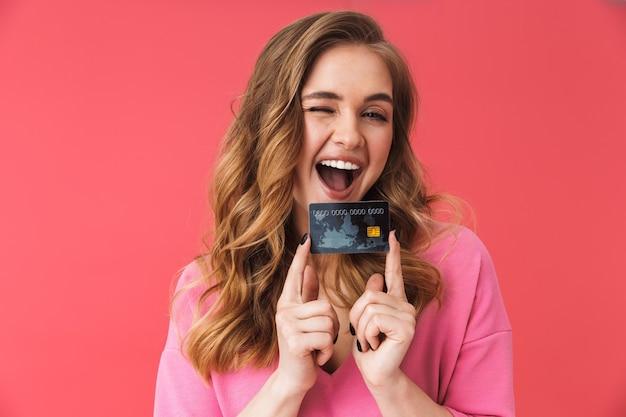 Belle jeune fille blonde décontractée debout isolée sur un mur rose, montrant une carte de crédit en plastique