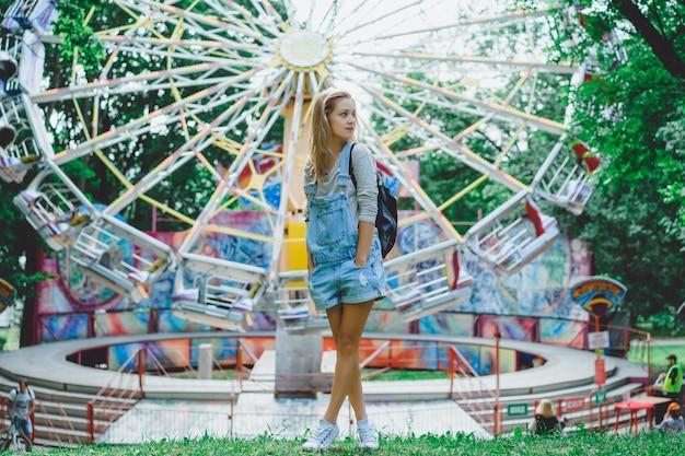 Belle jeune fille blonde en denim dans l'ensemble avec un sac à dos posant dans un parc d'attractions
