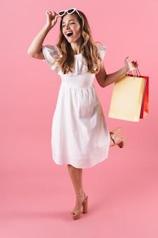 Belle jeune fille blonde joyeuse vêtue d'une robe d'été isolée sur un mur rose, portant des sacs à provisions
