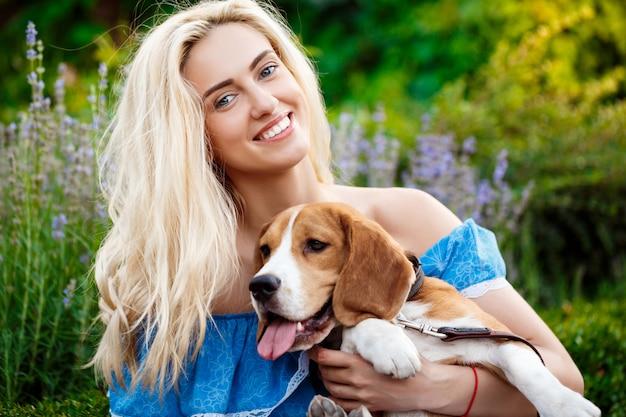 Belle jeune fille blonde marchant, jouant avec un chien beagle dans le parc.