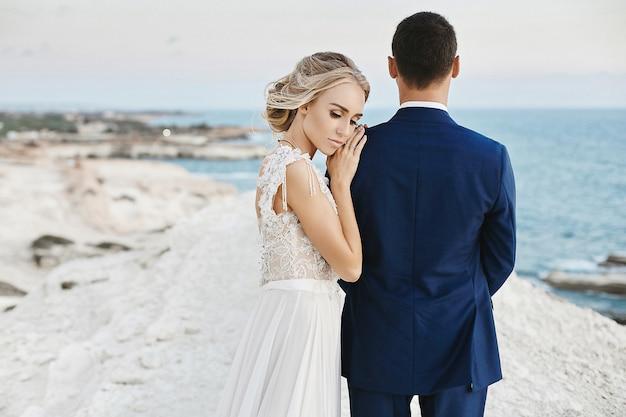 Belle jeune fille blonde modèle en robe de dentelle blanche à la mode s'appuyer sur le bel homme dans le costume bleu élégant et posant sur le rocher blanc sur la côte de la mer adriatique