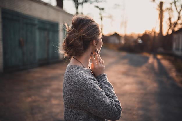 Belle jeune fille blonde modèle sourire. pull tricoté gris. sur le coucher du soleil. portrait. cheveux attachés en chignon