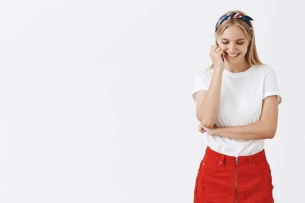 Belle jeune fille blonde posant contre le mur blanc