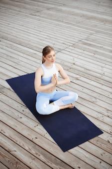 Belle jeune fille blonde souriante, pratiquer le yoga à l'extérieur.