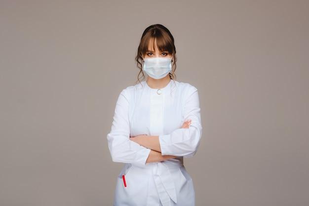Belle jeune fille en blouse médicale blanche, masque médical et bras croisés sur la poitrine