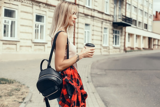 Belle jeune fille boit du café dans un verre dans la rue, rit et sourit