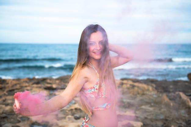 Belle jeune fille avec une bombe fumigène sur la plage