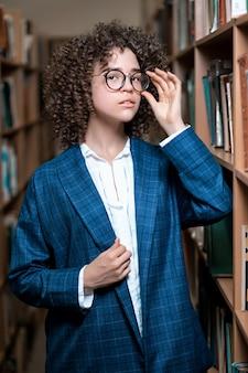 Belle jeune fille bouclée dans des verres et un costume bleu est debout dans la bibliothèque