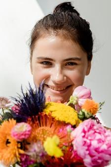 Belle jeune fille avec un bouquet de fleurs