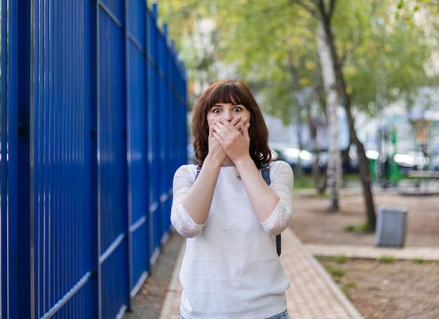 Une belle jeune fille brune a couvert sa bouche avec ses mains. surpris par le geste. une fille en veste blanche se tient dans la rue.
