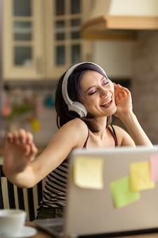 Une belle jeune fille brune dans la cuisine à la maison travaille sur un ordinateur portable et écoute de la musique dans des écouteurs