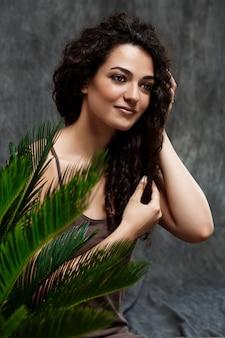 Belle jeune fille brune dans les plantes tropicales sur mur gris