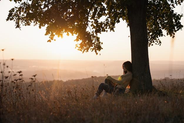 Belle jeune fille brune dans des vêtements décontractés, assis sous un grand arbre avec livre