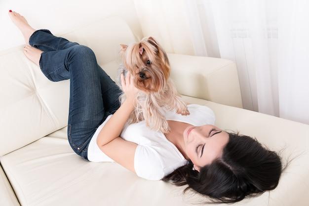 Belle jeune fille brune jouant avec son yorkshire terrier à la maison fixant au canapé et tenant son animal de compagnie