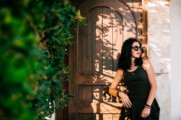 Belle jeune fille brune moderne à lunettes de soleil et une longue robe noire debout à une porte en bois