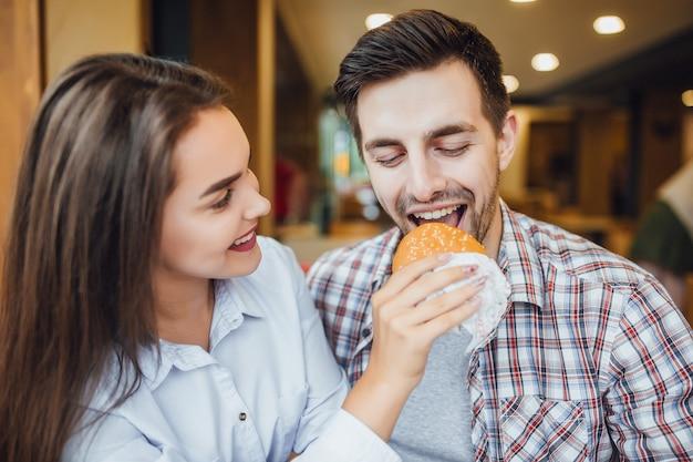 Une belle jeune fille brune nourrit le jeune chanceux caucasien avec un hamburger dans un fast-food.