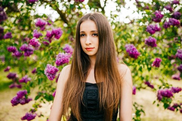 Belle jeune fille brune posant dans un parc fleuri.