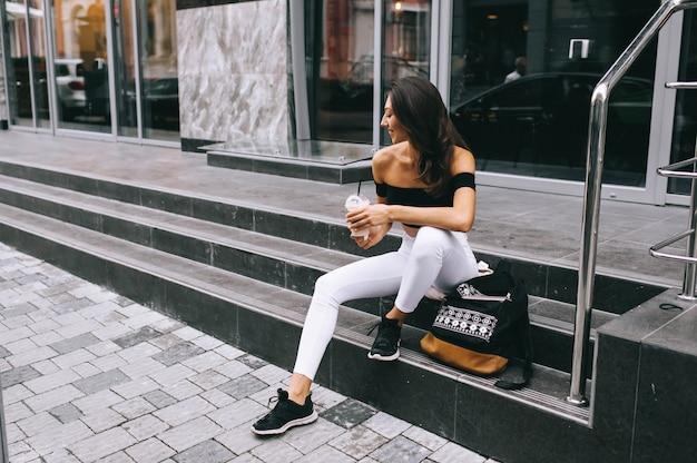 Belle jeune fille buvant du café dans la ville