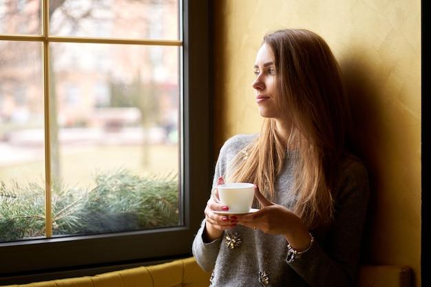 Belle jeune fille buvant du café ou du thé dans le café et regardant par la fenêtre.