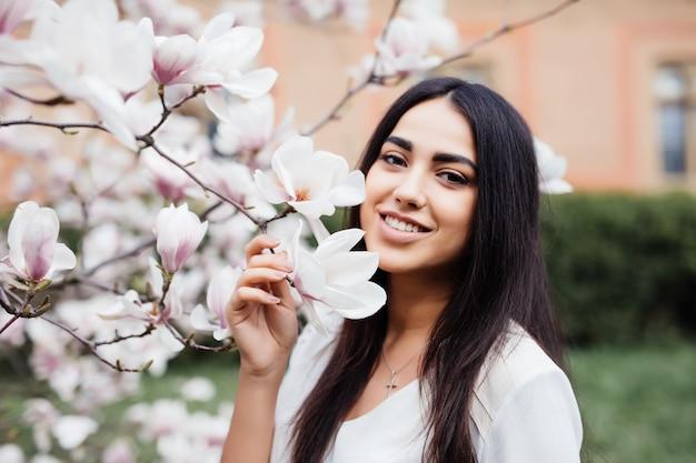 Belle jeune fille caucasienne dans un jardin de magnolia de printemps en fleurs. la jeune fille dans le jardin du matin. portrait, gros plan.