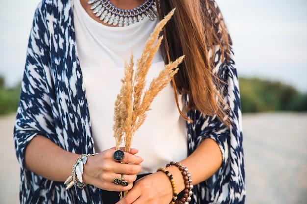 Belle jeune fille caucasienne dans des vêtements dans le style d'un boho avec beaucoup d'accessoires de bagues