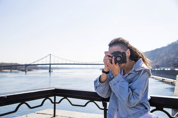 Belle jeune fille caucasienne avec des dreadlocks tenant un appareil photo rétro dans ses mains - photographie comme passe-temps en voyage