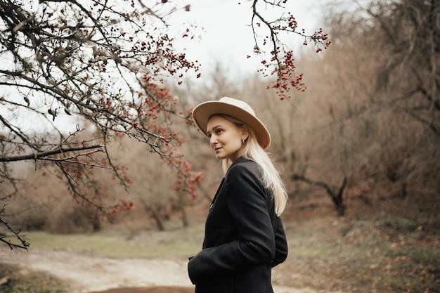 Belle jeune fille avec un chapeau près d'un arbre aux fruits rouges.