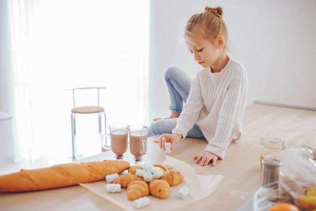 Une belle jeune fille avec des cheveux clairs en dentelle blanche et un pantalon bleu jeans assis à la maison