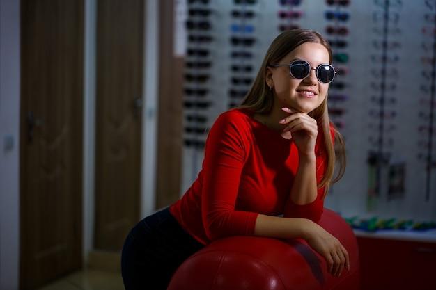 Belle jeune fille choisit des lunettes de soleil dans un magasin d'optique.