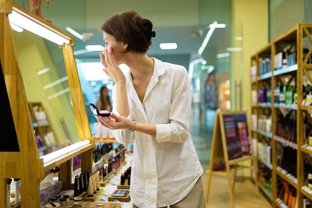 Belle jeune fille choisit sa crème ou poudre tonique et reprend le teint en face de grand miroir