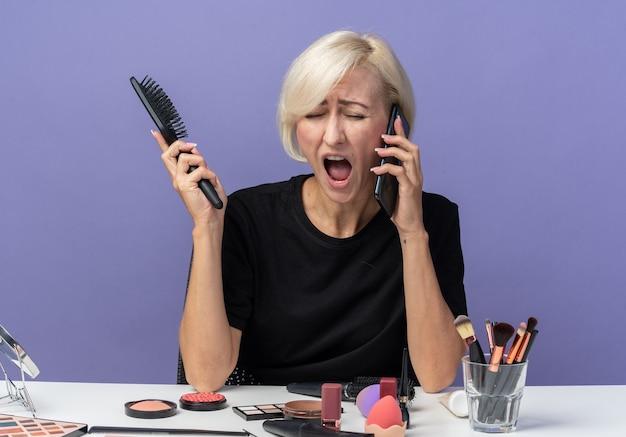 Une belle jeune fille en colère est assise à table avec des outils de maquillage parle au téléphone tenant un peigne isolé sur un mur bleu