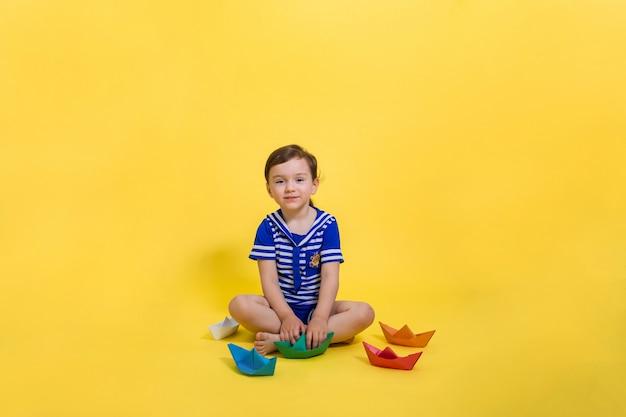 Une belle jeune fille en costume de marin est assise et tient un bateau en papier vert dans ses mains. espace libre sur un espace jaune. le jour de la marine.