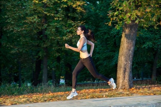 Une belle jeune fille court dans le parc pendant la saison fraîche au parc