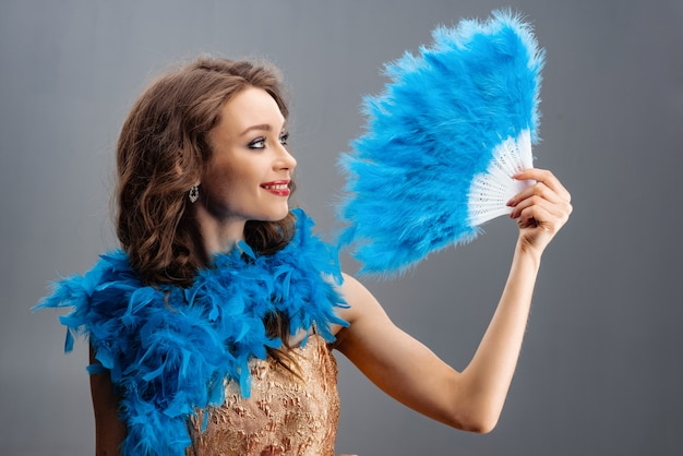 Belle jeune fille dans un boa bleu tenant un éventail de plumes à la main