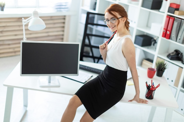 Une belle jeune fille dans le bureau s'assit sur la table et tenait un crayon rouge à la main.