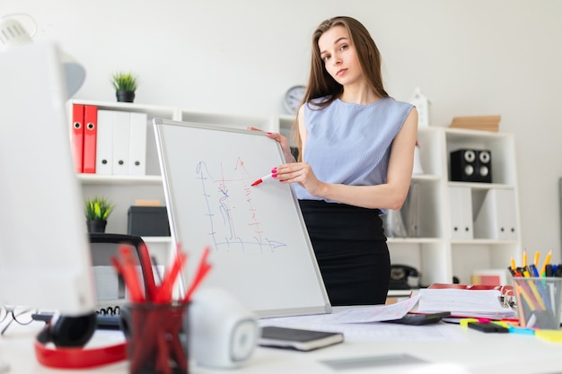 Une belle jeune fille dans un bureau se trouve près d'une table et explique sur un tableau magnétique un gravier.