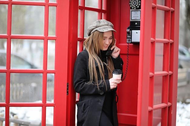 Belle jeune fille dans une cabine téléphonique. la fille parle au téléphone depuis la cabine téléphonique. cabine téléphonique anglaise dans la rue et une femme parlant au téléphone.
